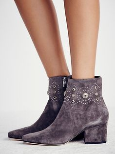Cailyn Heeled Boot   Suede ankle boots featuring a small block heel for a perfect lift and sleek pointed toe for a cool girl feel. Simple studs and decorative embellishments throughout. Exposed side zippers for an easy on-off.