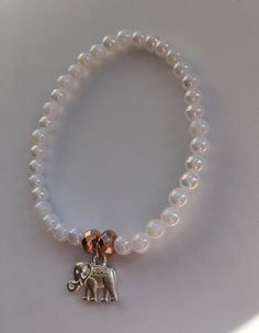 White beaded bracelet with a cute elephant charm at the centre! Elephant Jewelry, Animal Jewelry, Rose Gold Charms, Cute Presents, Prom, Homemade Jewelry, Hamsa Hand, Acrylic Beads, White Beads