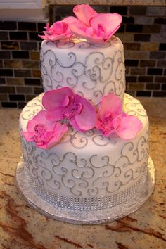 Sophisticated elegance.  Orchid cake with silver scrolls and a rhinestone band.