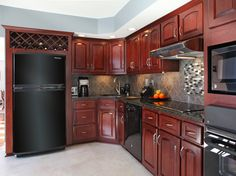 Cordovan on Cherry finish suits this arch styled cabinet door beautifully to reflect a traditional decor. The sleek Uba Tuba granite glistens beneath the charcoal backsplash. Cherry Wood Kitchen Cabinets, Cherry Wood Kitchens, Cherry Kitchen, Custom Kitchens, Luxury Kitchens, Home Kitchens, Remodeled Kitchens, Slate Floor Kitchen, Kitchen Flooring
