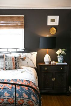 bed in front of window just simple woven roman shade. more casual look but dark paint makes room feel more intimate.