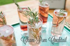 "delicious ""cham-pom"" cocktail with a sprig of rosemary"