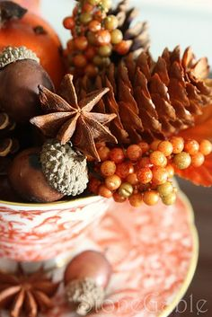 My fall tea cup holds acorns gathered from a trip to the mountains, tiny pinecones, star anise, small sprays of berry beads, a waxed leaf from my sugar maple, a faux leaf and a little round faux orange studded with real cloves and a star anise crown