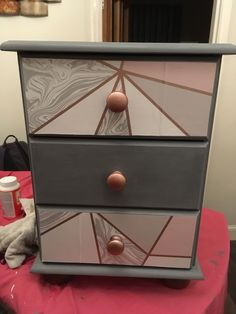 Upcycled bedside table - painted with grey chalk paint. Used samples of Zara marble effect wallpaper from ilovewallpaper.co.uk and some rose gold spray paint for the knobs