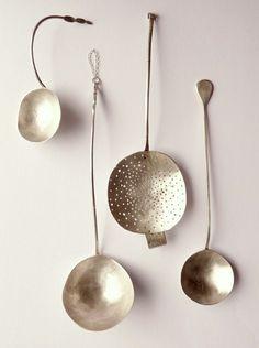 Kollektion aus silbernen Löffeln, gehängt an der Wand