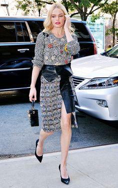 Kate Bosworth wears an embellished sweater, printed front-slit skirt, leather belt, top-handle bag, and black pumps