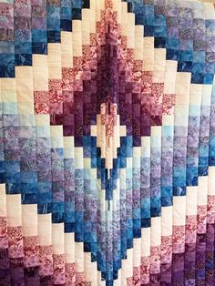 This beautiful Queen size quilt measures 96″ x 112″ and features a stunning floral border. The colors are shades of blue, purple and pink done in hand-dyed Batik materials.