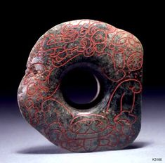 Maya. jade with red pigment. A vision serpent in the upper register. The lower register seems to be an offering with a kin sign as its predominant feature. width 7.0 cm..