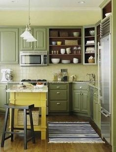 Yellow painted island gives a nice pop of color in this soft, green-painted kitchen.