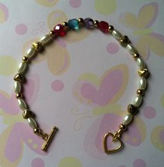 Family Bracelet Starting with Moms Birthstone (Dec), children's (Dec & Feb) & ending with Dads (Jan). Made with 4x7mm Pearls, Czech crystals with Gold tone Hearts. Sold