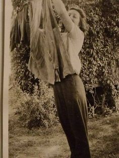 Vintage photo from the 1940s of a Woman hanging clothes on the line.