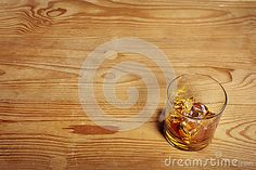 Whiskey alcohol glass with ice cubes coctail on wooden desk