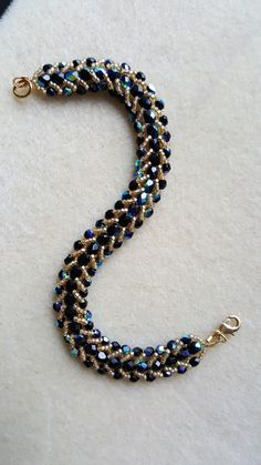 This piece combines two of my favorite things - jet AB beads, and flat spiral stitch! Two sizes of jet AB Czech firepolished glass beads and gold seed beads come together to form this beautiiful and e