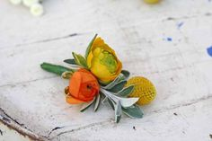Yellow And Orange Ranunculus with Senecio and Billy Balls. Spring Button Hole