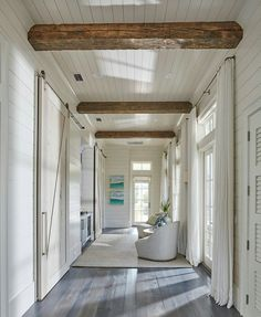 Floor to ceiling shiplap paneling with reclaimed wood beam. This hallway boasts rustic wood beam ceiling, shiplap walls, shiplap ceiling as well a wall of French doors and transom windows dressed in white cotton curtains. Shiplap Paneling, Shiplap Ceiling, Ceiling Beams, Hallway Ceiling, Plank Ceiling, Shiplap Wood, Upstairs Hallway, Long Hallway, White Ceiling