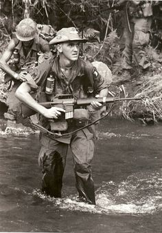 Specialist from 1st Bn, 327th Airborne Infantry Regiment. Jump wings on black and yellow oval pinned to side of boonie hat. Vietnam