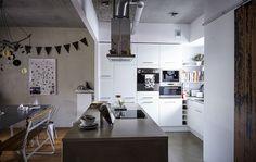 Weiße Elemente in Kombination mit einer Kücheninsel lassen eine moderne, offene Küche entstehen.