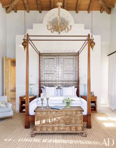 The master bedroom's Réplicas y Originales Ornelas bed in a Mexican vacation home by designer Marshall Watson is set against tin doors that open onto the adjacent bath.