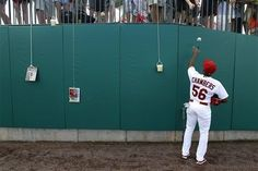 St. Louis Cardinals' Adron Chambers tosses a ball to a fan after autographing it before a spring training baseball game against the Miami Marlins in Jupiter, Fla., Friday, March 16, 2012. (AP Photo/Patrick Semansky)