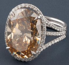 Bague en or gris ornée d'un diamant ovale dans un entourage de diamants, l'anneau orné de lignes de diamants. Poids du diamant: 12,03 carats. Couleur: Fancy Brown Yellow. Avec certificat de l'Institut Américain de Gemmologie GIA. Poids 6,5 g