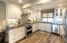 kitchen.  White kitchen cabinets, stainless steel appliance, tile backsplash.  White kitchen, grey kitchen, blue kitchen.