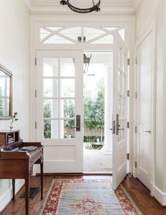 Glass-paned double doors and glass transom, lovely small desk and mirror.  Beautiful blue hall runner with red border.