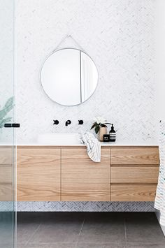 Love the vanity unit (wood could be more rustic looking) with thinner basin on top and taps out of wall. Don't like round mirror or wall tiles.