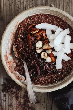 Chocolate coconut quinoa breakfast, topped with toasted nuts, nourishing and energizing.