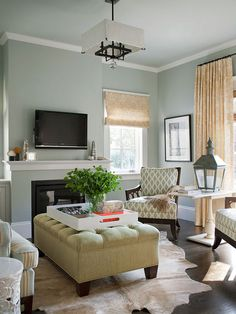 Comfy, Yet Chic:: The small living room at the front of the house functions as a grown-up space for entertaining. The colors here mimic those used in the rest of the house. An extra-large ottoman provides feet-up relaxation and also serves as a coffee table. great to bring the room in if you have opposing doors. Love this idea for our living room. We have a similar space!