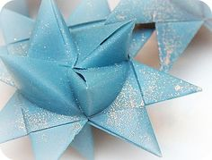 I've seen these described as German or Swedish paper stars.  One of my favorite craft projects.  I would make hundreds of these at the holidays to give as gifts.  The folding is really easy once you get the hang of it.  Dipped in paraffin and dusted with glitter, they're lovely and last for years.