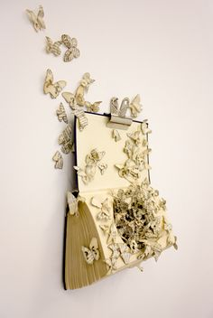 Book art is my favorite! Use a bulldog clip to hang a book on the wall.