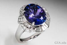 5.59 carat (ct) oval tanzanite contrasted with 28 channel set tapered baguettes and 12 round brilliant cut diamonds.