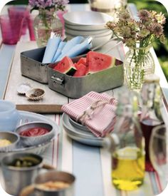 Fantastic outdoor table setting. Steel containers, striped linens, vintage glassware