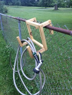 """DIY Hose holder for fence. Treated 2x2s and some 3"""" screws. Nice next to the garden boxes."""