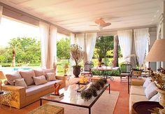 Essa varanda é uma sala de estar, cheia de móveis e adornos, tem até tapete! As cortinas são leves e complementam muito bem a decoração do ambiente. Foto: Revista Casa e Jardim.