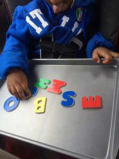 Magnetic letters on a cookie sheet. Melissa and Doug wooden magnetic alphabet letters are colorful and come in both upper and lower case $11.25.  You can either get an old one from the pantry to pay $2 like I did. Used this on a spring break road trip with my 3 year old. Also serves as a tray for eating in the car and coloring.