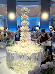 Sylvia and Emily hard at work!!! Can you tell where the real flowers and sugar flowers are placed?      A Sylvia Weinstock creation! Love her work.     #weddingcakes #sylviaweinstock