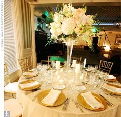 To accommodate the number of guests (185), the reception was held inside. Tables alternated with a mix of tall and short floral arrangements and were topped off with ivory table linens and gold chiavari chairs.