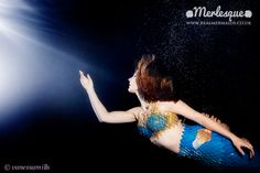 Beautiful underwater photograph of Merlesque mermaid performer Lorelei reaching toward the moonlight filtering down from the surface of the water. Find out more about Merlesque at: http://www.realmermaids.co.uk