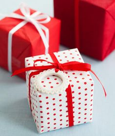 Sweet packages with handmade ornaments. Love, love, love that polka dot paper and red ribbon...