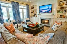 Like the short, wide fireplace with large TV & big, square coffee table