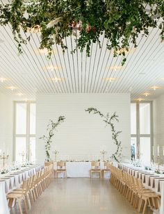 These two vines of crawling greenery against white wooden panels make a bold statement in their simplicity, serving as the sole backdrop for the bridal party table and whole reception.