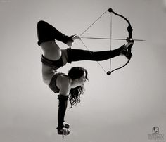 Girl doing a handstand, holding a bow with her legs