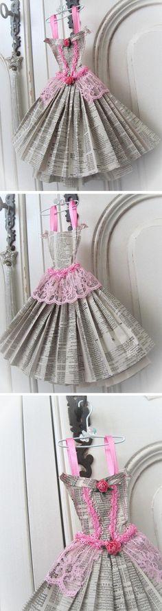 Robe faite à partir de pages d'annuaire téléphonique. Elle est cousue avec du fil de coton rose et est garnie de bretelles en ruban de satin. Elle est ornée de galons, de dentelle et de deux fleurs en papier dans les tons de rose. Elle mesure 24.5 cm de hauteur x 22 cm de largeur et est livrée avec son petit cintre blanc.