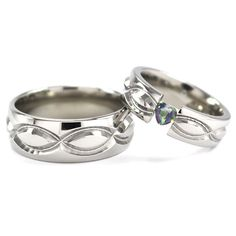 Beautiful Titanium Matching rings featuring milled Infinity Symbols surrounding the band with the Woman's ring featuring a stunning Heart Shaped gemstone of your choosing, sold on Renaissance Fine Jewelry.