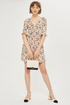 In textured cream fabric, this charming floral print mini dress is a summer favourite. Featuring a v-neck and back, tie detail, half sleeves and frilly cuffs, it's further enhanced with eyelet and frill accenting to the waist. We're wearing it with slingback heels this season.