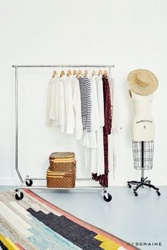 A home office space with a simple rolling rack, a mannequin, and a brightly woven area rug