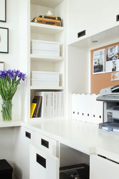 Sleek home office with glossy white built-in cabinetry, shelving and desk area with inset black hardware.