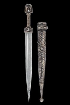 Caucasian kindjal/'kama' (dagger).  Late 19th century.  Straight, double-edged blade, with two fullers on the front face and one fuller on the back face; wooden grip and sheath completely silver-plated and richly decorated with bas-relieved and nielloed floral motifs and beaded bands on the front face; chape with oval sphere, smooth front part with nielloed racemes.