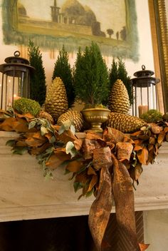 Beautiful mantel for now into Thanksgiving and Christmas.  Magnolia, large gilded pine cones, small spruce trees, lanterns and ribbon.  Love this!